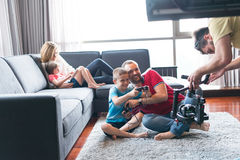 Happy family playing a video game. Happy family. Father, mother and children playing a video game Father and son playing video games together on the floor Royalty Free Stock Photos
