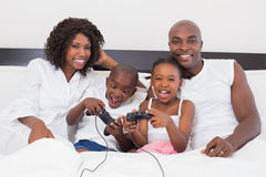 Happy family playing video games together in bed Royalty Free Stock Images