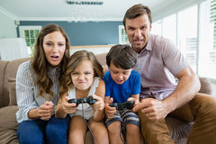 Happy family playing video games together in living room Royalty Free Stock Photo