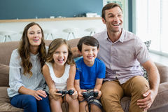 Happy family playing video games together in living room Stock Image