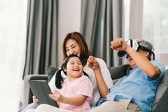 Happy family playing Virtual Reality game together, young kid girl using digital tablet, grandfather wearing VR headset stock photo
