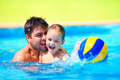 Happy family playing in water polo in the pool. Happy father and son playing with ball in pool, summer sport Royalty Free Stock Images