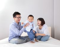 Happy family playing on white bed Stock Image