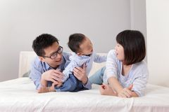 Happy family playing on white bed Stock Photography