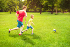 Happy family plays football in sunny park Stock Image