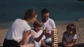 Happy family plays jenga game near lake stock video