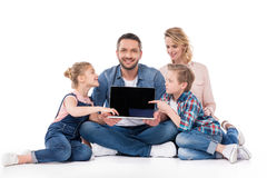Happy family pointing on blank screen of laptop while sitting on floor Royalty Free Stock Photo