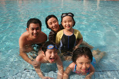 Happy family in the pool. One happy family playing in the pool Stock Photography