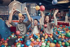 Happy family in pool with balls Stock Photos