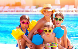 Happy family at the pool. Happy big family having fun at the pool, spending summer vacation together, wearing funny colorful sunglasses, enjoyment and pleasure Royalty Free Stock Photography