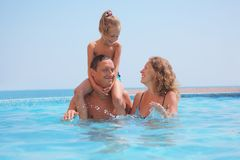 Happy family in pool on sea background. Stock Images