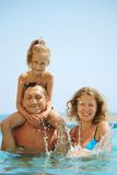 Happy family in pool. Splashing water. Stock Image