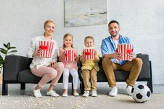 Happy family with popcorn boxes sitting on sofa and smiling. At camera stock images