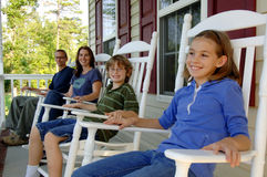 Happy family on porch. A happy family of four sitting in rocking chairs on a front porch Royalty Free Stock Photo