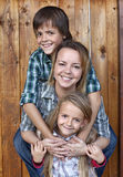 Happy family portrait against wooden wall Royalty Free Stock Photography
