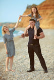 Happy family portrait on the beach. Father and mother walking wi Stock Photography
