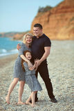 Happy family portrait on the beach. Father and mother walking wi Stock Photos