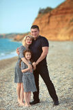Happy family portrait on the beach. Father and mother walking wi Royalty Free Stock Photography