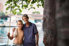 Happy family portrait of boy and grandpa hugging. Family portrait with happy boy and grandfather hugging and smiling at camera after fishing near river Stock Photos