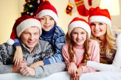 Happy family. Portrait of four happy family members in Santa caps looking at camera with smiles Royalty Free Stock Photos