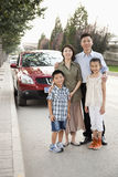 Happy Family Portrait in Front of Car on Roadside Stock Photo