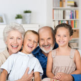 Happy family portrait. With a loving elderly couple hugging their laughing young granddaughter and grandson while posing in the living room Stock Image