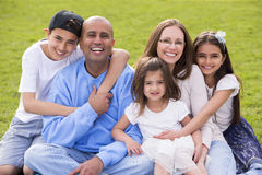Happy Family. A portrait of a mixed ethnicity family, mum and dad have three cute children between the ages of 4 to 10. They are sitting down and smiling happily Royalty Free Stock Image