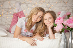 Happy family portrait. Mother and daughter hugging in bed in pajamas and looking at the camera. Loft interior Royalty Free Stock Photo