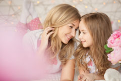 Happy family portrait. Mother and daughter laying on bed and smiling. Loft interior. Background with lights. Pastel Royalty Free Stock Images