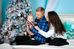 Happy family portrait - mum, dad, little son at a beautiful Christmas tree stock photos
