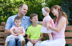Happy family portrait on outdoor, group of five people sit on wooden bench in city park, summer season, child and parent Stock Photography