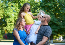 Happy family portrait on outdoor, group of four people posing in city park, summer season, child and parent Stock Image