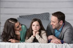 Happy family portrait. Family portrait of happy parents and their daughter laying on bed at home Royalty Free Stock Photos