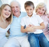 Happy family. Portrait of senior couple with their daughter and grandson looking at camera at home Stock Photo