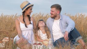 Happy family portrait, young couple sits together close to their child girl daughter in open air outings in harvest stock video