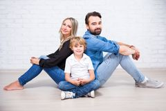 Happy family portrait - young parents and little son sitting on. The floor over white brick wall background Stock Photo