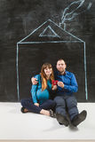 Happy family posing against house drawn on chalkboard Royalty Free Stock Image