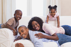 Happy family posing on the couch together Stock Image