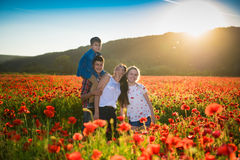 Happy family posing on the poppy field Stock Photography