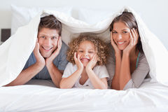 Happy family posing under a duvet Stock Photography
