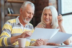 Positive aged couple being involved in paperwork at home Royalty Free Stock Photography
