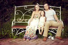 Happy family pregnant mom, father and daughter in the summer sit. On a Park bench and embrace. Woman and men looking at the camera, and the girl laughs Royalty Free Stock Photo