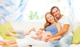 Happy family. pregnant mother, father, and child daughter at hom. Happy family. pregnant mother, father, and child daughter on sofa at home Royalty Free Stock Images