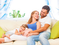 Happy family. pregnant mother, father, and child daughter at hom. Happy family. pregnant mother, father, and child daughter on sofa at home Stock Photos