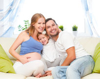 Happy family. pregnant mother, father, and child daughter at hom. Happy family. pregnant mother, father, and child daughter on sofa at home Stock Image