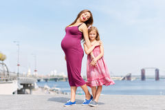 Happy family, pregnant mother and her daughter little girl child walking and hugging on the embankment in the summer day Royalty Free Stock Images