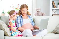 Happy family pregnant woman and child with a laptop at home Royalty Free Stock Images