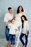 Happy family with pregnant woman and children posing in the studio royalty free stock photo