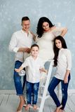 Happy family with pregnant woman and children posing in the studio stock photos