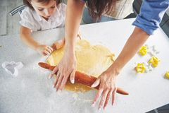 Happy family preparation holiday food concept. Family cooking Christmas cookies. Hands of mother and daughter preparing. The dough on the table. Happy family in royalty free stock photos